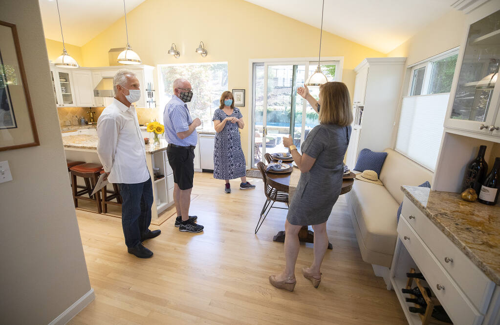 From right, real estate agent Tammra Borrall shows off the kitchen of an east Santa Rosa home to Patty and Mark Bowers of San Jose, and their agent Ed Heinz on Thursday, August 20, 2020.  (Photo by John Burgess/The Press Democrat)