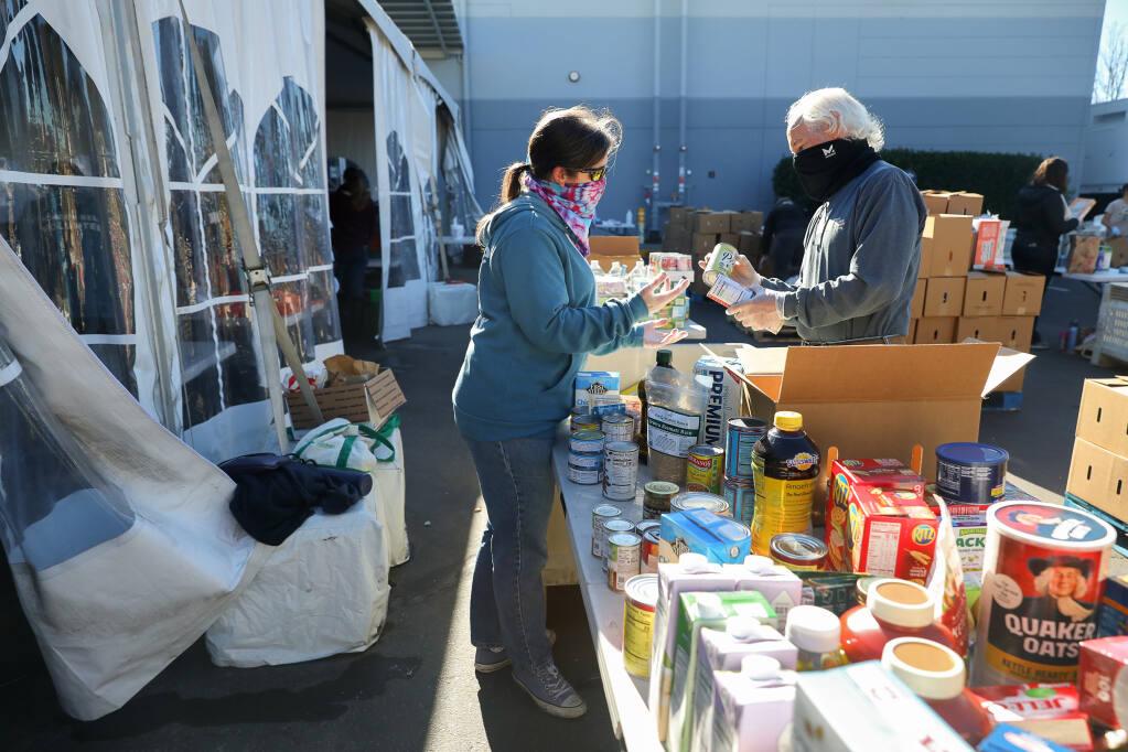 Denise and Rick Degraf sort donated food at Redwood Empire Food Bank in Santa Rosa on Monday, Nov. 23, 2020.  (Christopher Chung/ The Press Democrat)
