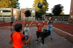 Children play an improvised basketball game using a barbecue as the basket, at Puerta Villa apartments in Santa Rosa, California, on Thursday, June 6, 2019. (Alvin Jornada / The Press Democrat)