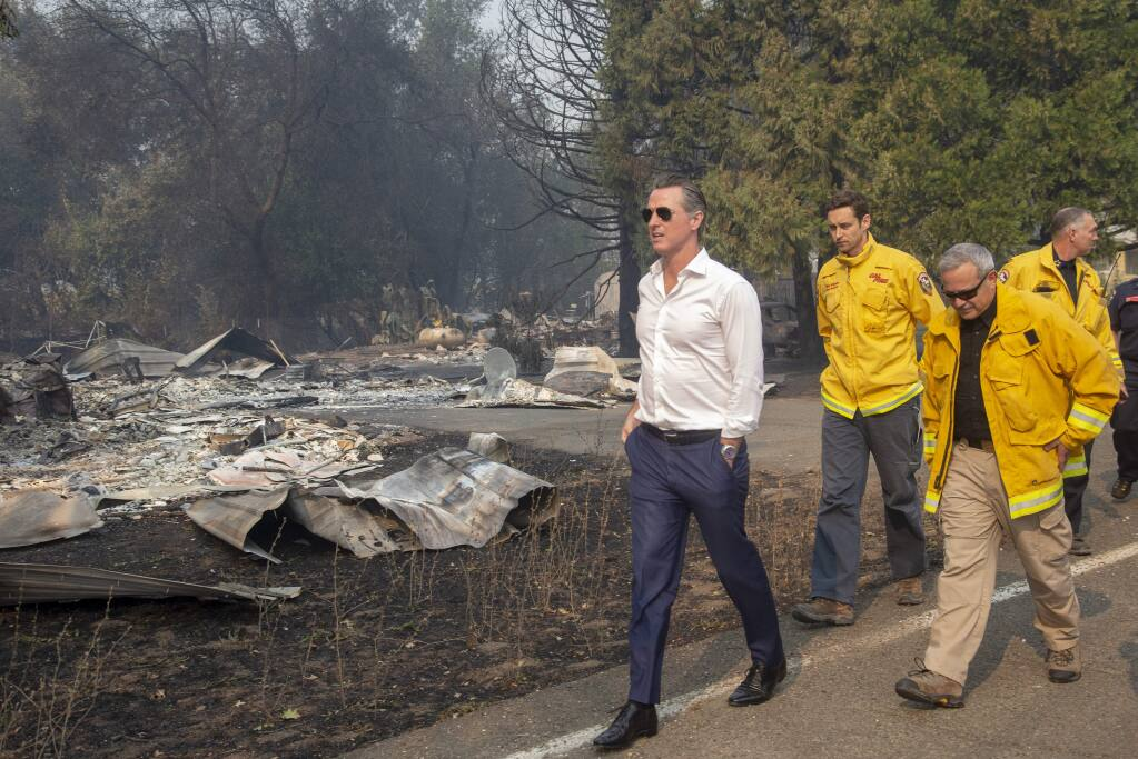 Gov. Gavin Newsom passes a burned home in Geyserville during a Friday tour of damage caused by the Kincade fire. (KARL MONDON / San Jose Mercury News)