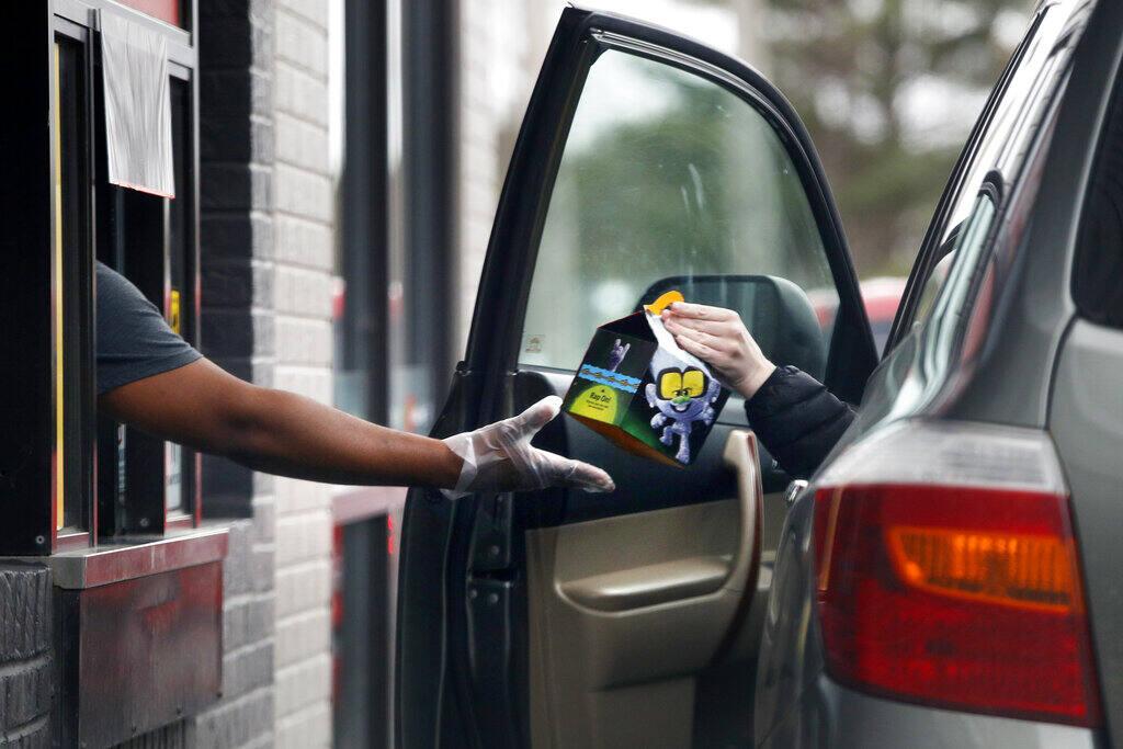 A worker at McDonalds hands a customer a Happy Meal. (ROBERT F. BUKATY / Associated Press)