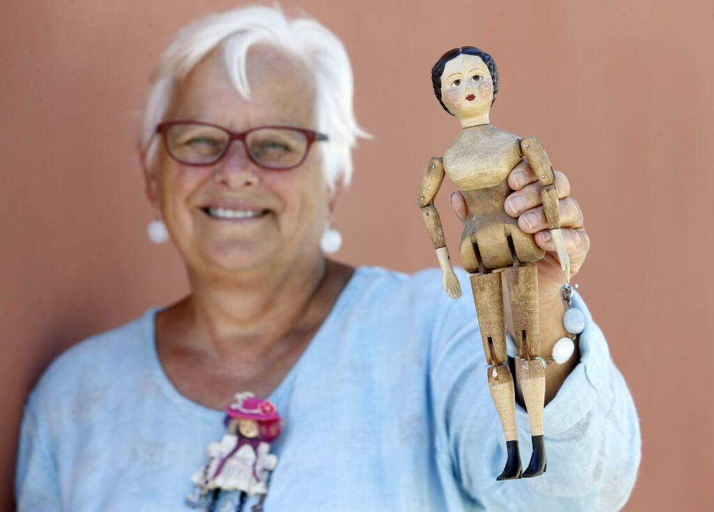 Dr. Geri Olson, the co-curator of the exhibit 'Journeys Through Light and Dark: Dolls as Tellers of Stories' holds a Joel Ellis style doll that she carved and will be featured in the exhibit at the Petaluma Arts Center. Photo taken at the Petaluma Arts Center on Thursday, June 30, 2016 in Petaluma, California . (BETH SCHLANKER/ The Press Democrat)