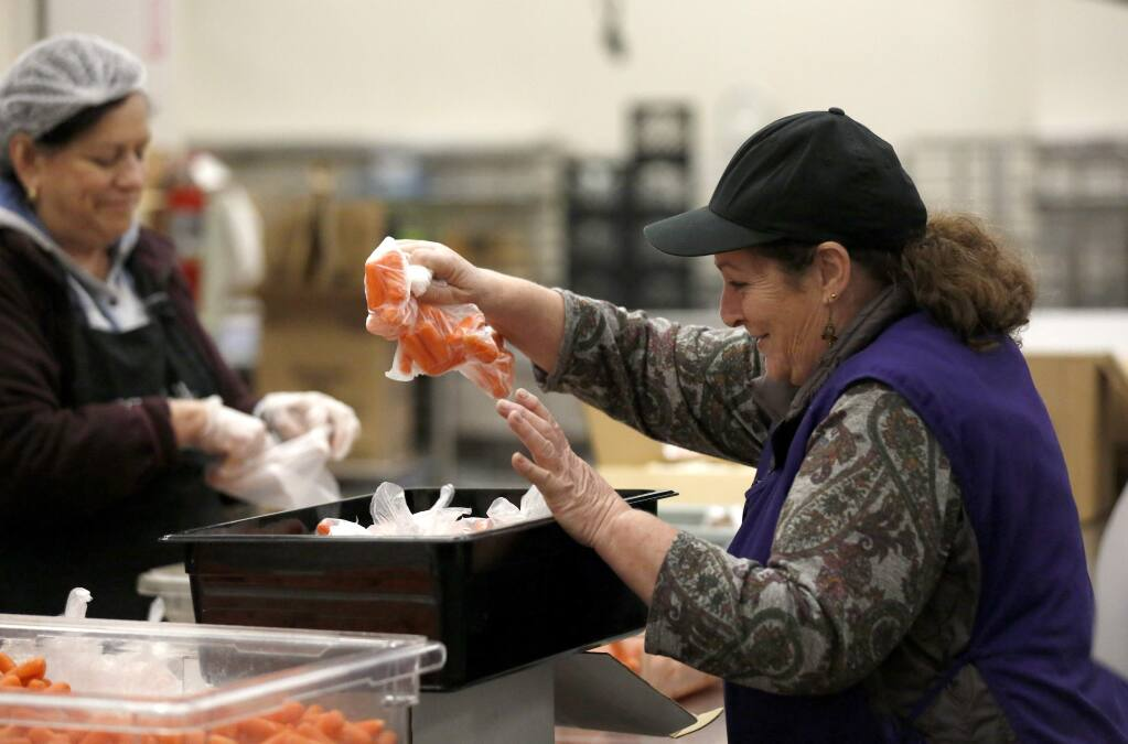 Line leader Olive Brandalick helps pack bag of individually wrapped carrots for free lunches available to TK-12 students to pick up at select school sites in Santa Rosa. Photo taken Santa Rosa City Schools Child Nutrition Services kitchen in Santa Rosa on Monday, March 23, 2020. (BETH SCHLANKER/ The Press Democrat)