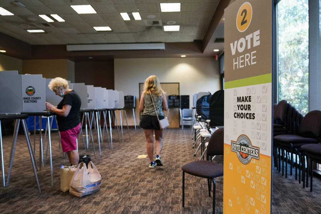 Voters cast ballots in Huntington Beach during the early voting period for the California gubernatorial recall election. (ASHLEY LANDIS / Associated Press)