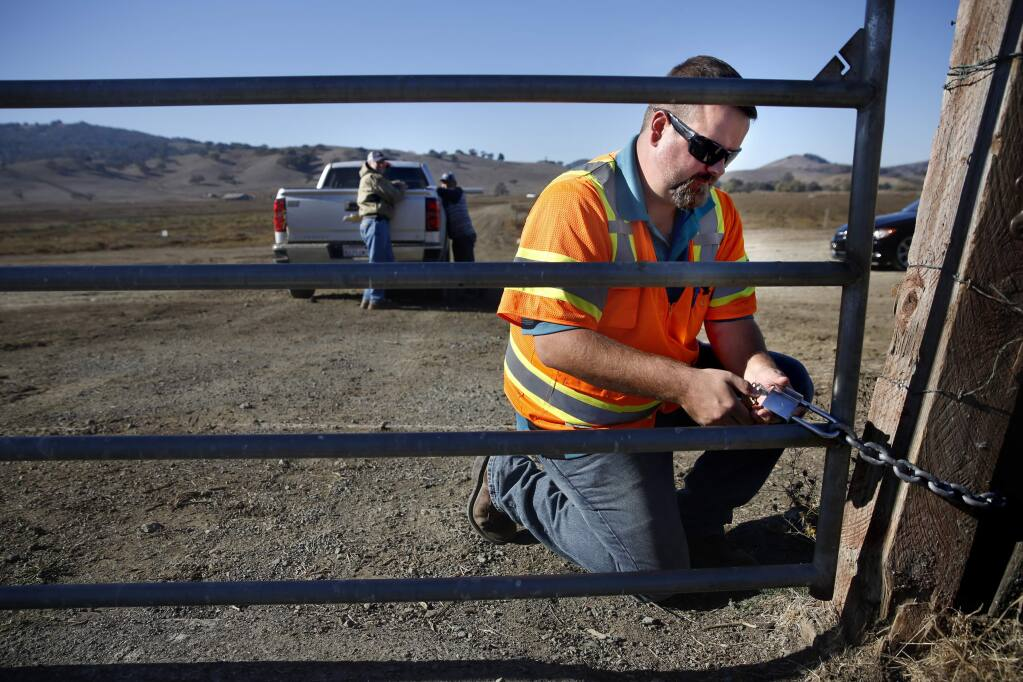 SMART controller supervisor Dennis Bush locks a gate along the SMART rail line after allowing Jerry Corda to cross the tracks in his pickup in order to feed cattle on the ranch in Petaluma, on Thursday, November 12, 2015. (BETH SCHLANKER/ The Press Democrat)