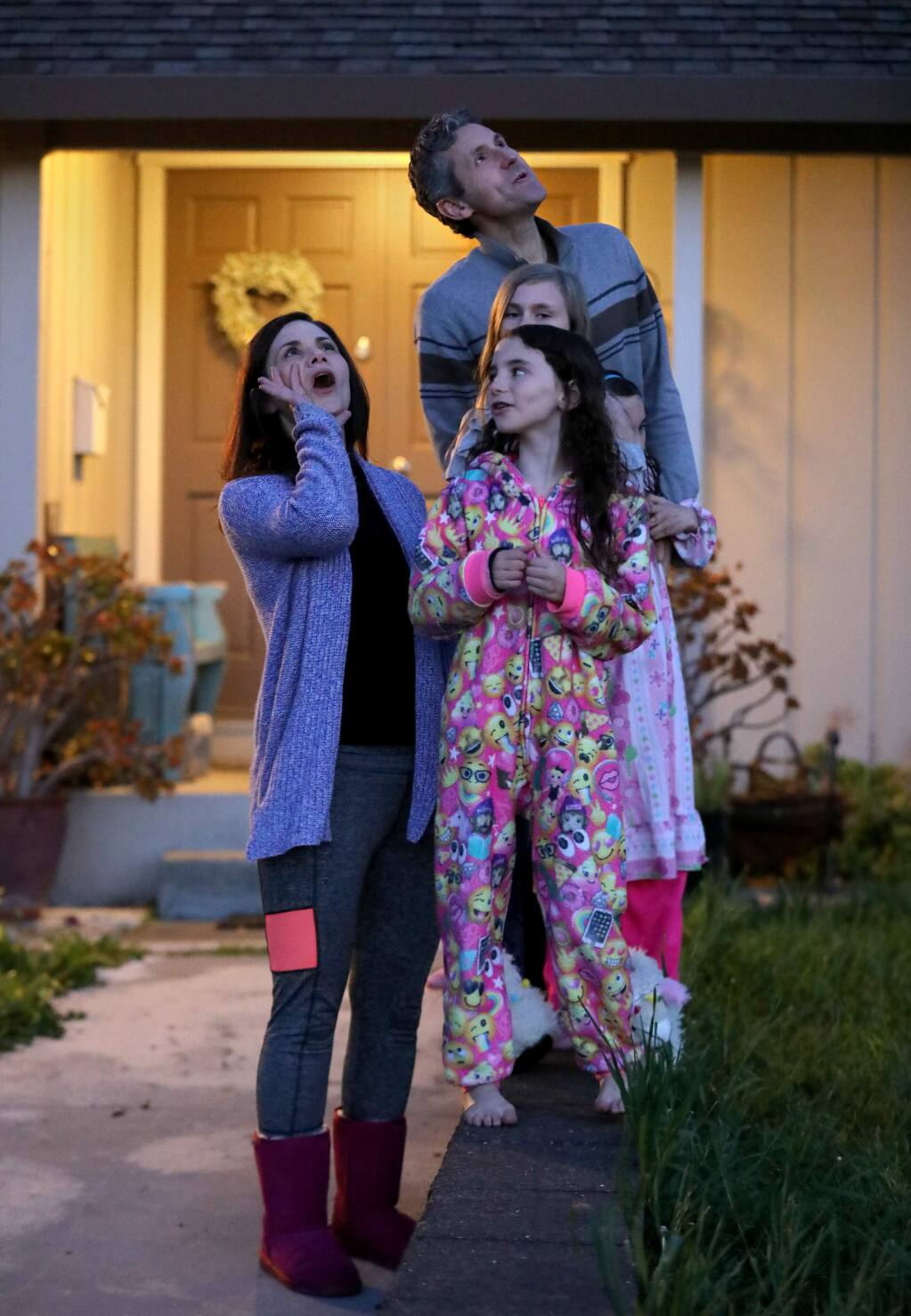Noelle Mullen, her daughters Tatum, 8, front, Willow, 11, and Fallon, 8, (not seen) and her husband, Dan, join with neighbors and howl outside their home at 8pm in Petaluma on Tuesday, April 7, 2020. (BETH SCHLANKER/ The Press Democrat)