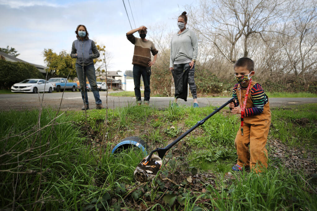 From right, Logan Shmatovich, 5, picks up trash around the corner from Valley Ford Road on Thursday, Feb. 18, 2021. Looking on are members of a new group called Soil Growers, including his grandmother, Niki Shmatovich, Saill White and Terry Church, who will be picking up garbage on a 2 1/2-stretch of Valley Ford Road under a new Sonoma County Adopt A Road program. (Beth Schlanker / The Press Democrat)