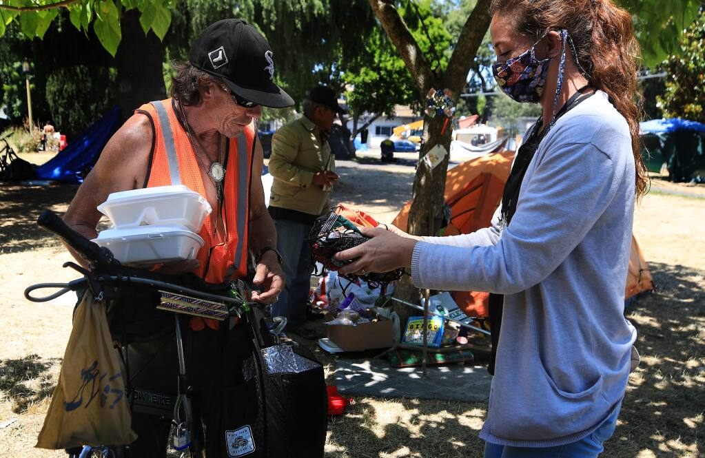 Patrick Preston gets the pick of face masks from Sheryl Rood of Sonoma Applied Village Services at a homeless camp in Fremont Park in Santa Rosa, Tuesday, July 23, 2020.  (Kent Porter / The Press Democrat) 2020