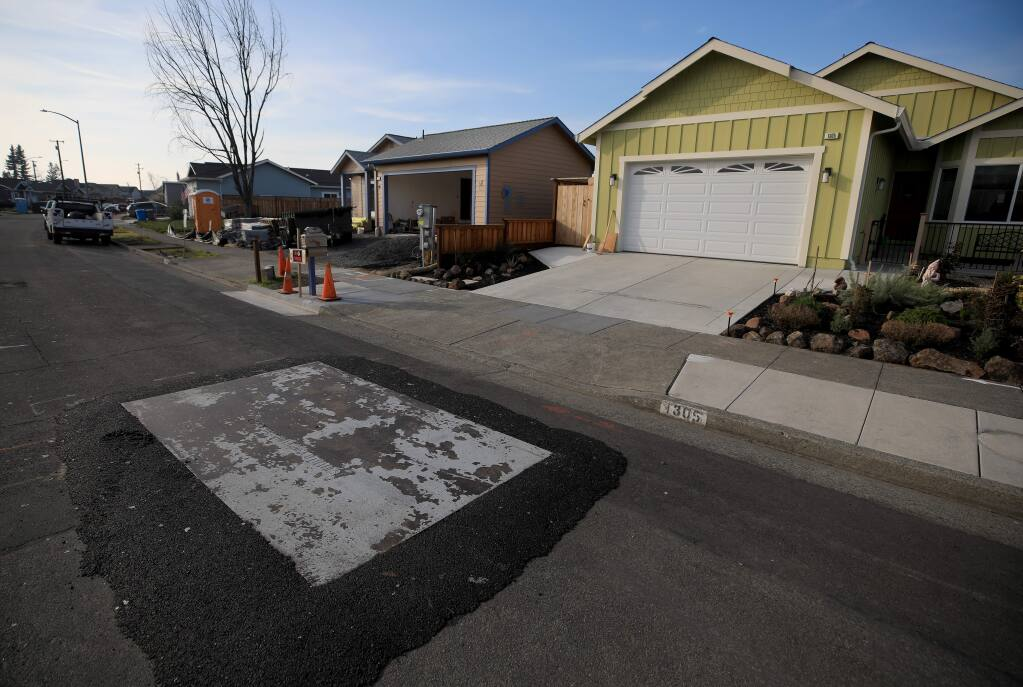 A metal plate covers a PG&E breach of a sewer line on Cashew Road in Coffey Park, that is causing homeowners sewer lines to back up, Friday, Jan. 3, 2020 in Santa Rosa. (Kent Porter / The Press Democrat) 2020