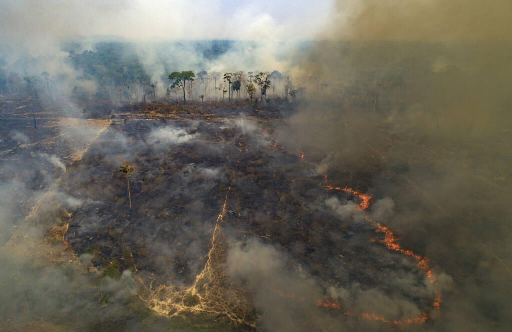 FILE - In this Aug. 23, 2020, file photo, fire consumes land recently deforested by cattle farmers near Novo Progresso, Para state, Brazil. Climate-connected disasters seem everywhere in the crazy year 2020. But scientists Wednesday, Sept. 9, say it'll get worse. (AP Photo/Andre Penner, File)