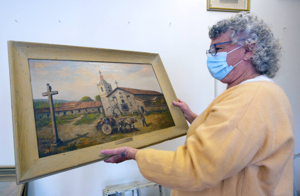 Patricia Cullinan, director of the Depot Park Museum, examines one of the Mission in Santa Clara which had been hanging in the Bank of America on Napa Street, on Monday, Feb. 1. (Photo by Robbi Pengelly/Index-Tribune)