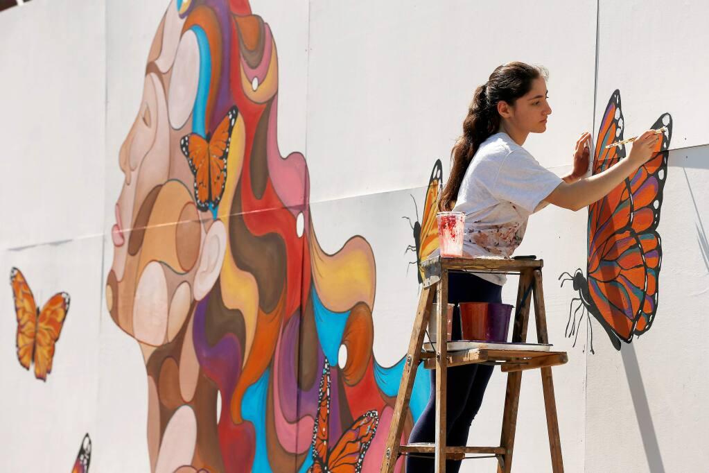 Montgomery High School junior Rima Makaryan, 16, paints details on the Dreamer Mural she created at Montgomery High School in Santa Rosa, California, on Saturday, March 30, 2019. (Alvin Jornada / The Press Democrat)