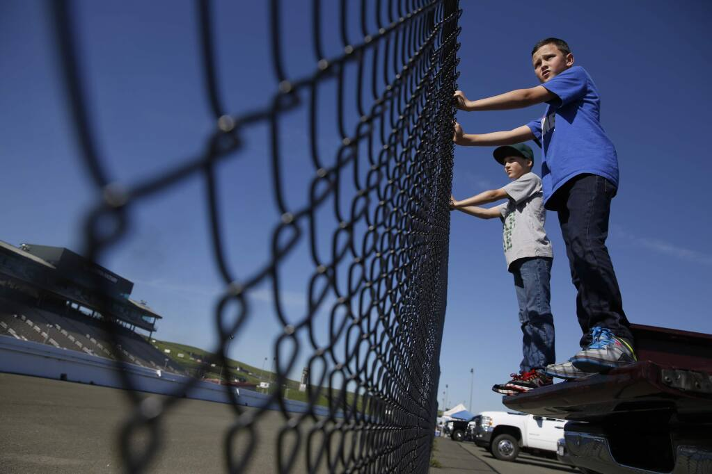 Cody West, 10, front, and his twin brother Justin watch drag racing from the back of a pick-up truck at Sonoma Raceway on Monday, Feb. 16, 2015 in Sonoma. (BETH SCHLANKER/ PD FILE)