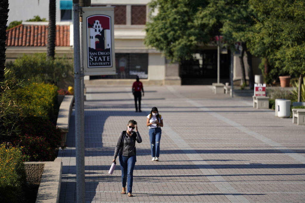 People walk on campus at San Diego State University Wednesday, Sept. 2, 2020, in San Diego. San Diego State University on Wednesday halted in-person classes for a month after dozens of students were infected with the coronavirus. (AP Photo/Gregory Bull)