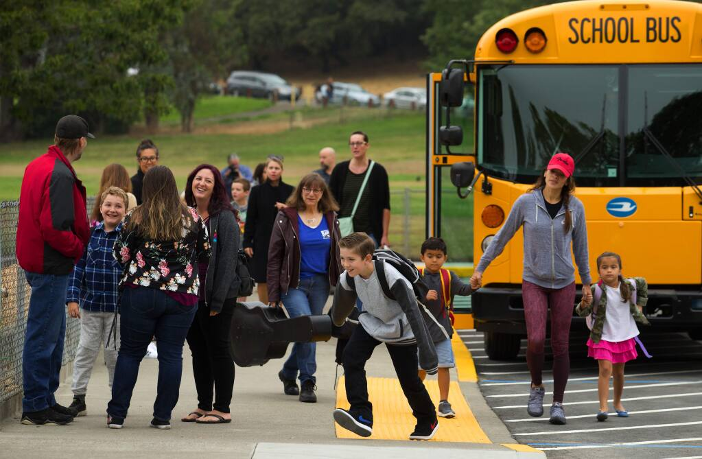 (FILE PHOTO) Families gather to reconnect in the drop-off area at Hidden Valley Elementary School in Santa Rosa on the first day of the school year in 2018. (John Burgess/The Press Democrat, 2018)
