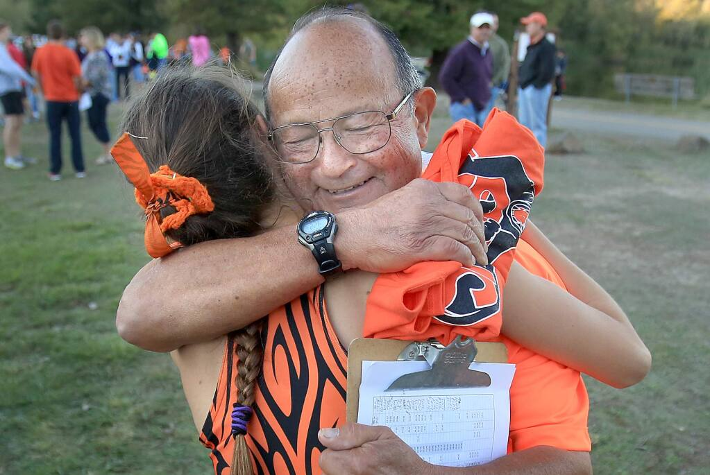Santa Rosa's Delaney White is congratulated by her coach, Doug Courtemarche, after White won her fourth straight NBL cross country title at Spring Lake in Santa Rosa, Friday Nov.6, 2015. (Kent Porter / Press Democrat)