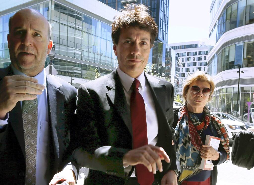FILE - In this May 21, 2019 file photo, Agustin Huneeus, center, arrives at federal court in Boston, to plead guilty to charges in a nationwide college admissions bribery scandal. Huneeus was scheduled to be sentenced on Friday, Oct. 4. (AP Photo/Michael Dwyer, File)