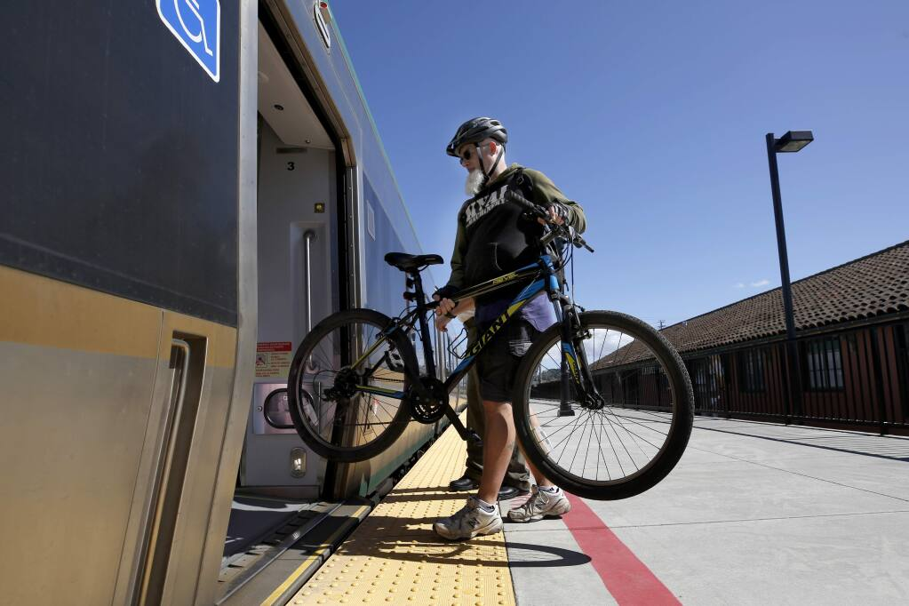 A cyclist loads his bicycle onto a northbound SMART train at the station in Petaluma, California, on Thursday, March 21, 2019. (BETH SCHLANKER/ PD)