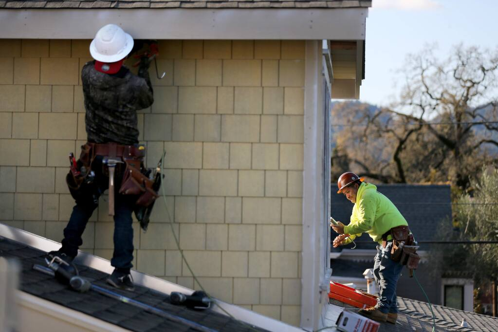 Contractors work to install fire resistant fiber-cement shingles on a new home on Lincoln Street being built by Hybridbuild Inc. in Healdsburg on Monday, Dec. 23, 2019. (BETH SCHLANKER/ The Press Democrat)