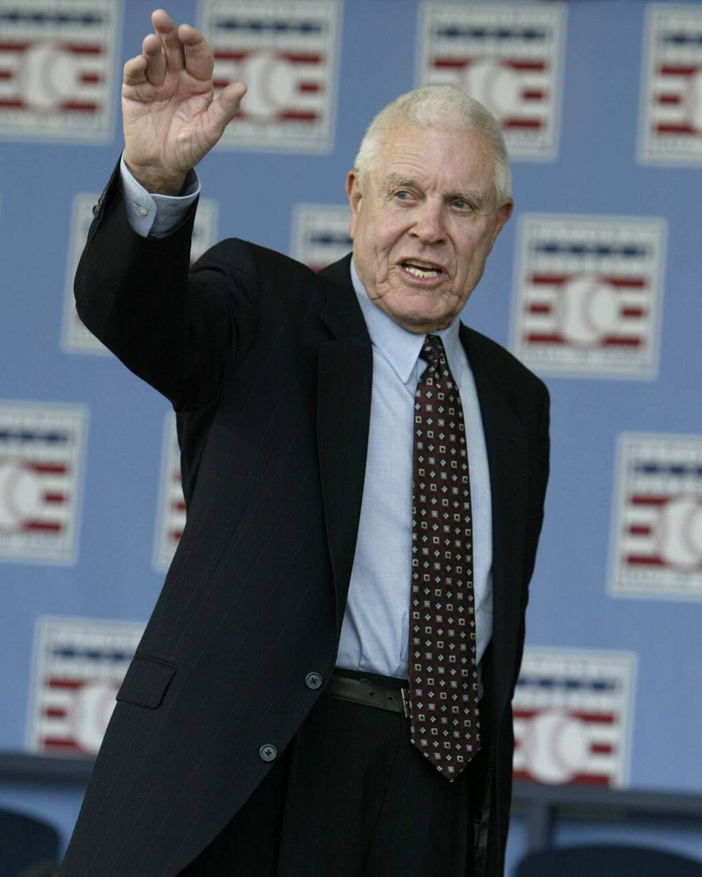 In this July 25, 2004, file photo, broadcaster Lon Simmons, the longtime voice of baseball in the San Francisco Bay area, waves at the end of the 2004 National Baseball Hall of Fame induction ceremonies in Cooperstown, N.Y. The Giants announced that Simmons had died Sunday, April 5, 2015. He was 91. (AP Photo/John Dunn, File)