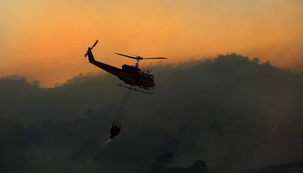 A Cal Fire helicopter heads to the Cold fire near Lake Berryessa, Tuesday, Aug. 2, 2016. (KENT PORTER/ PD)