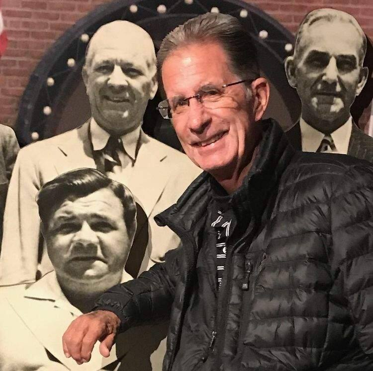 Pete Dardis poses in front of a montage of baseball greats while visiting the Baseball Hall of Fame in Cooperstown, New York, in June. (Photo from Dardis family)