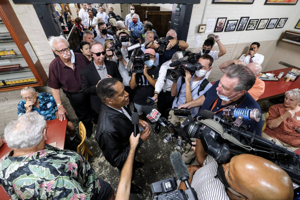 Republican conservative radio show host Larry Elder, is surrounded by media while he visiting Philippe The Original Deli during a campaign for the California gubernatorial recall election on Monday, Sept. 13, 2021, in Los Angeles. (AP Photo/Ringo H.W. Chiu)