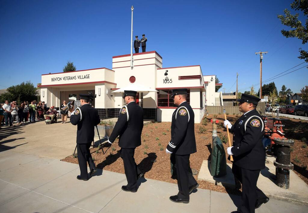 The Santa Rosa Fire Department honor guard, from left, Chris Matthies, Chris Roberts, Scott Byrn and Teddy Day start off the grand opening of the Benton Veterans Village in Santa Rosa, Friday, October 19, 2018 in Santa Rosa. On top of the building presenting colors are Andrew Vallely, left and Mike Musgrove. (Kent Porter / The Press Democrat) 2018