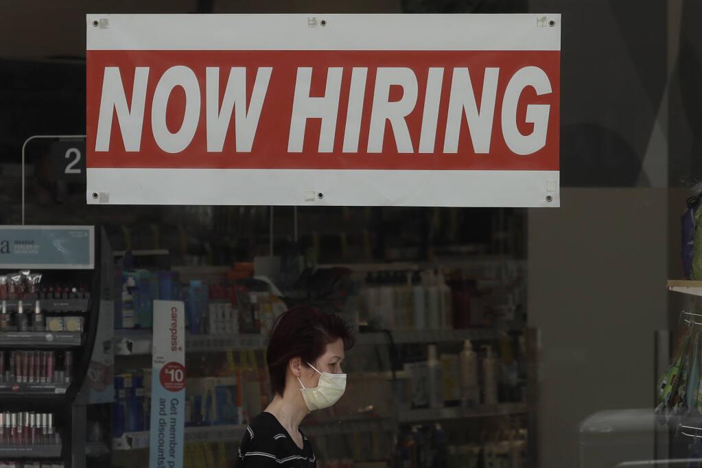 A woman wears a mask during the coronavirus outbreak while walking under a Now Hiring sign at a CVS Pharmac yin San Francisco, Thursday, May 7, 2020. (AP Photo/Jeff Chiu)