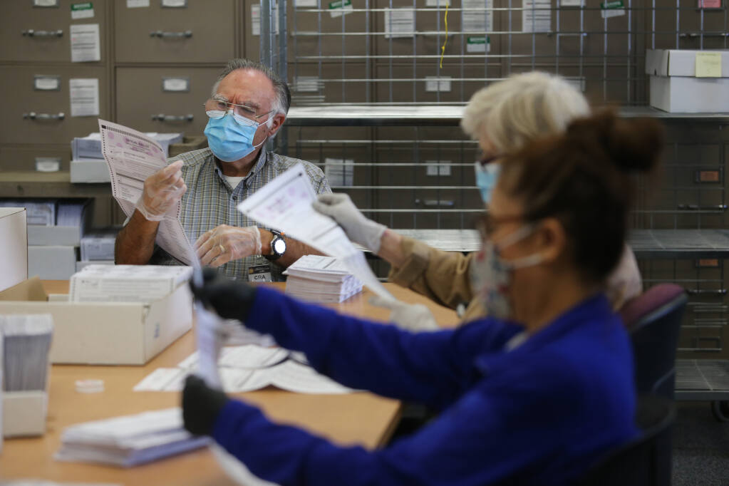 Extra help employee David Tatro checks for any potential problems with a ballot before it is run through the voting machine at the Sonoma County Registrar of Voters Office in Santa Rosa, Calif., on Monday, Sept. 13, 2021. (Beth Schlanker/The Press Democrat)