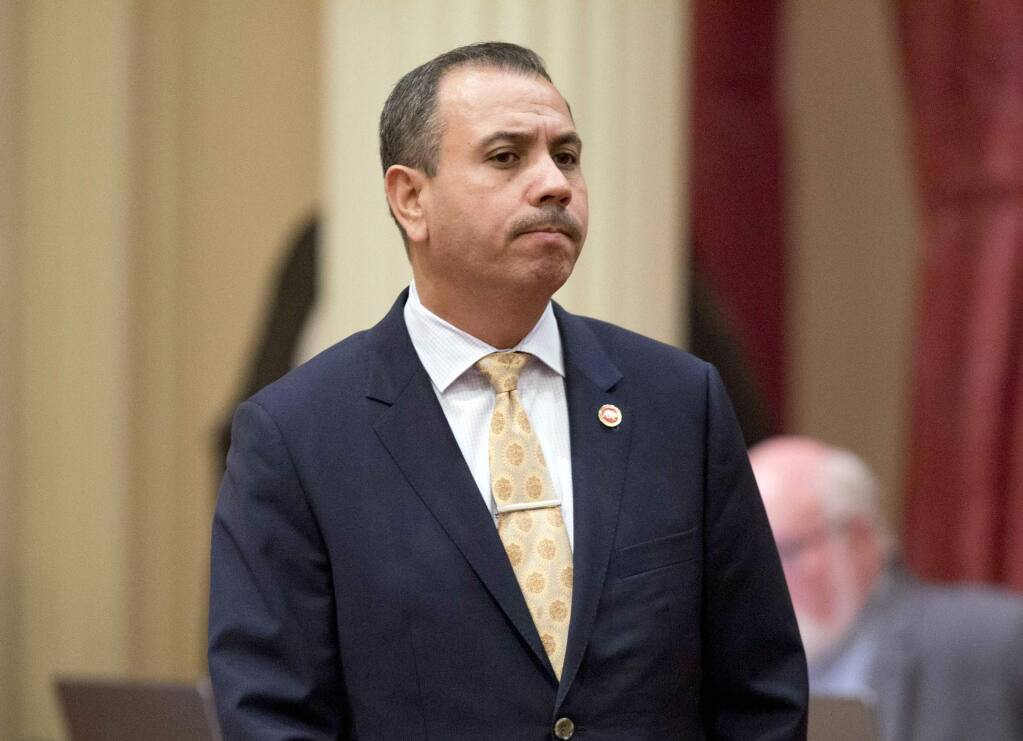FILE - In this Jan. 3, 2018 file photo, state Sen. Tony Mendoza, D-Artesia, stands at his desk after announcing that he will take a month-long leave of absence while an investigation into sexual misconduct allegations against him are completed, in Sacramento, Calif. He ultimately resigned his seat, but is again running for the seat in the upcoming California primary election. (AP Photo/Steve Yeater, File)