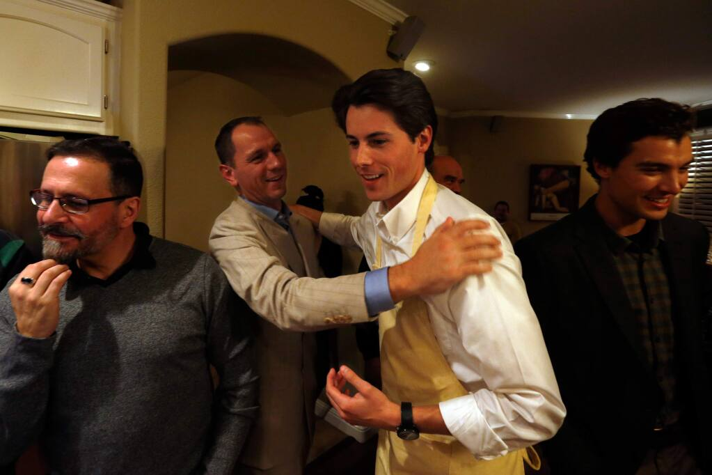 Jack Tibbetts, second from right, is congratulated by supporter Peter Rumble after they saw initial election results showing Tibbetts among the top four candidates during an election night party at Tibbetts' home in Santa Rosa, California on Tuesday, November 8, 2016. (Alvin Jornada / The Press Democrat)