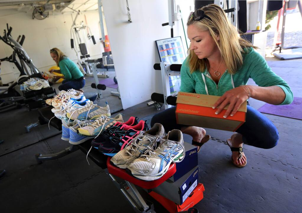 PHOTO: 2 by JOHN BURGESS / The Press Democrat -Gym teacher Myriah Volk stores donated athletic shoes in her Sebastopol home.