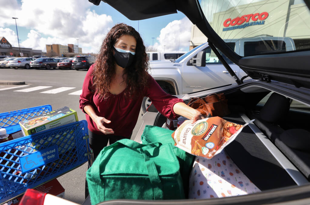 Sienna Hornback packs her groceries into her car at Costco in Rohnert Park on Tuesday, February 2, 2021.  Hornback decided to wear two masks for added protection against the coronavirus and its new variants.  (Christopher Chung/ The Press Democrat)