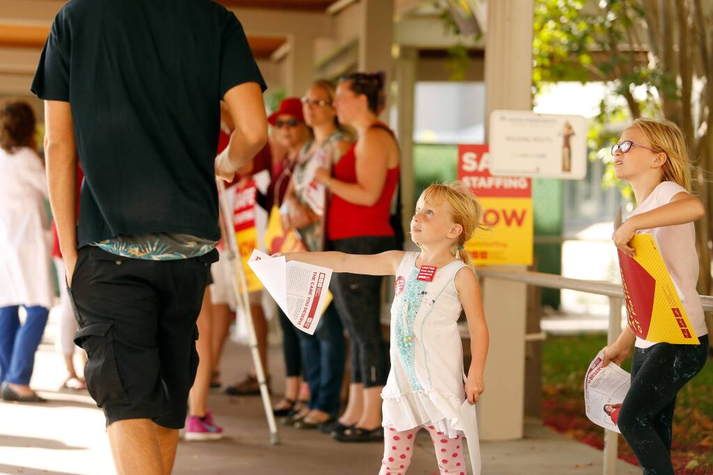 Amber Bottasso, 5, and her older sister Sophia, 7, whose mother is a Kaiser Permanente emergency room nurse, hand out informational flyers to passersby during a rally by Kaiser nurses who are negotiating for safer staffing levels to reduce wait times and prevent downgrades in patient care, outside Kaiser Permanente Hospital in Santa Rosa, California on Monday, September 18, 2017. (Alvin Jornada / The Press Democrat)