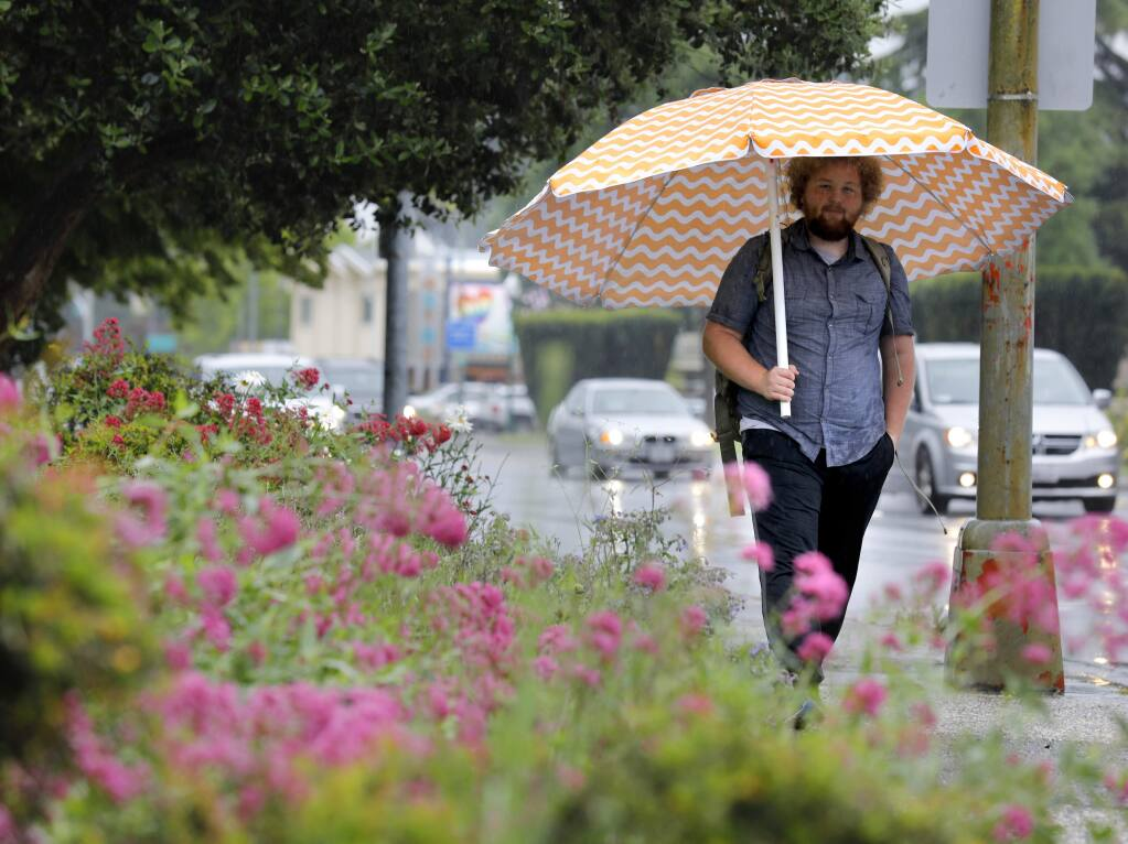 Jack Lupin uses a beach umbrella to stay dry as he walks down Santa Rosa Avenue in Santa Rosa on Wednesday, May 15, 2019. (BETH SCHLANKER/ PD)