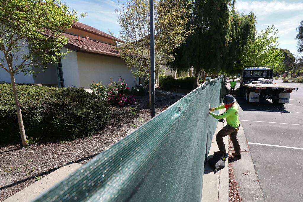 John Rainwater, with Kenwood Fence Co., works on attaching privacy screening onto a fence around the Sauvignon Village residence halls, on the Sonoma State University campus in Rohnert Park on Monday, April 27, 2020. (Christopher Chung/ The Press Democrat)