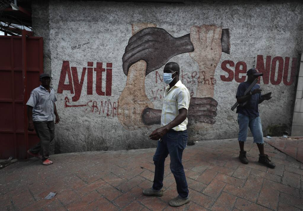 Demonstrators walk past a mural that reads in Creole 'Haiti is us' during anti-government protests in Port-au-Prince, Haiti, Friday, Oct. 11, 2019. Protesters burned tires and spilled oil on streets in parts of Haiti's capital as they renewed their call for the resignation of President Jovenel Moïse just hours after a journalist was shot to death. (AP Photo/Rebecca Blackwell)