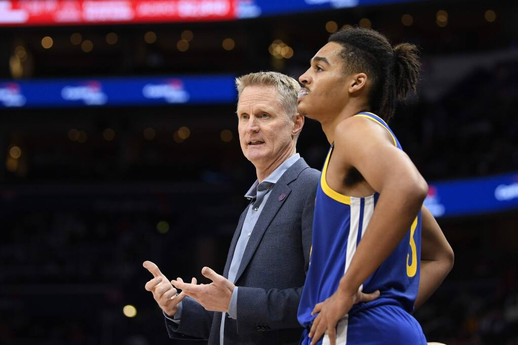Golden State Warriors head coach Steve Kerr, left, talks with guard Jordan Poole, right, during the first half against the Washington Wizards, Monday, Feb. 3, 2020, in Washington. (AP Photo/Nick Wass)