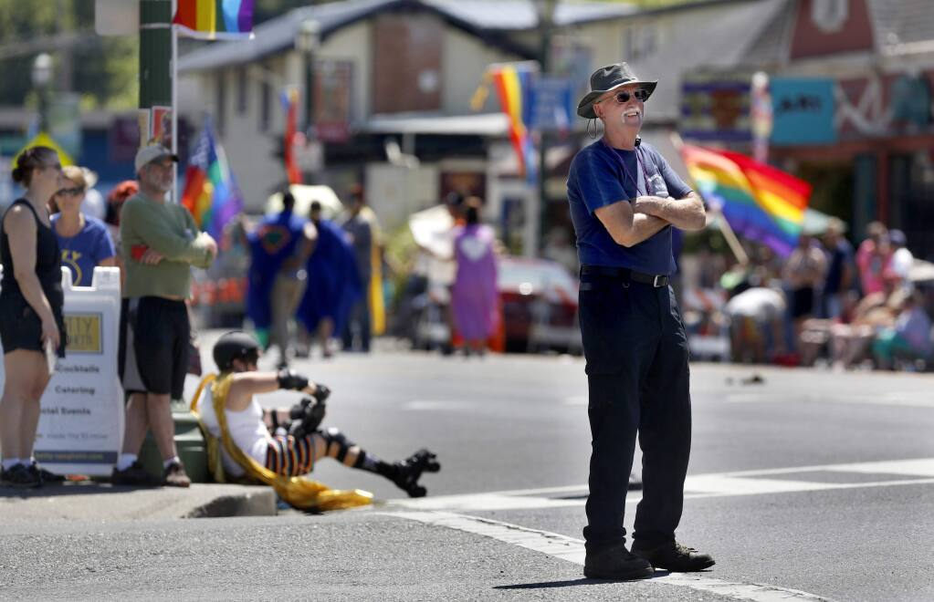 Monte Rio Fire Chief Steve Baxman takes a moment from directing traffic to watch the Sonoma County Gay Pride Parade in Guerneville, on Sunday, June 5, 2016. (BETH SCHLANKER/ The Press Democrat)
