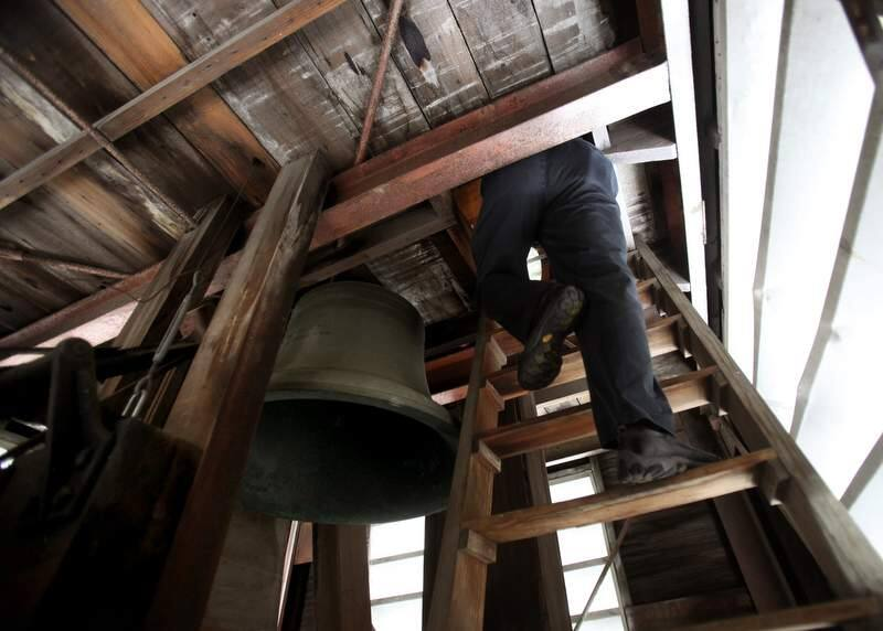 John Roche enters the top of the clock tower in Empire Building on Courthouse Square past the bell forged in 1908. (John Burgess/The Press Democrat)