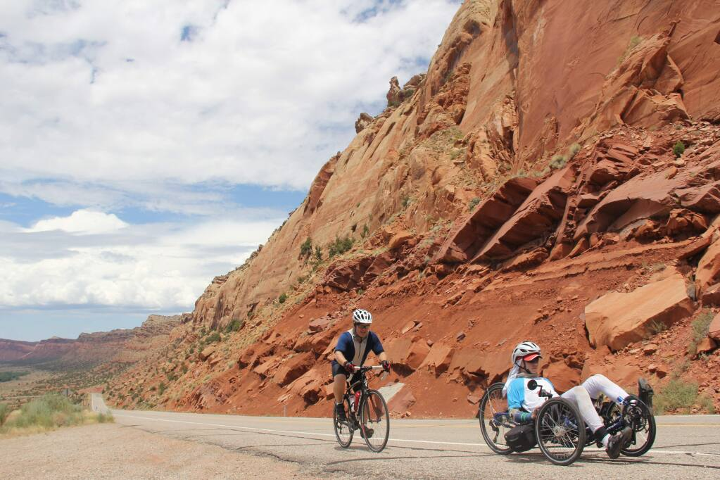 Tucker Cullen, 15, followed by his father Shawn Cullen, cycle outside of Capitol Reef, Utah during Tucker's marathon ride across the United States. (Photo by Anne Cullen)