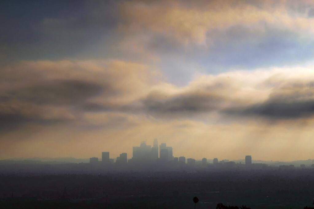 FILE - In this Oct. 26, 2018, file photo, downtown Los Angeles is shrouded in early morning coastal fog and smog. General Motors, Fiat Chrysler, Toyota and many others in the auto industry are siding with the Trump administration in a lawsuit over whether California has the right to set its own greenhouse gas emissions and fuel economy standards. (AP Photo/Richard Vogel, File)