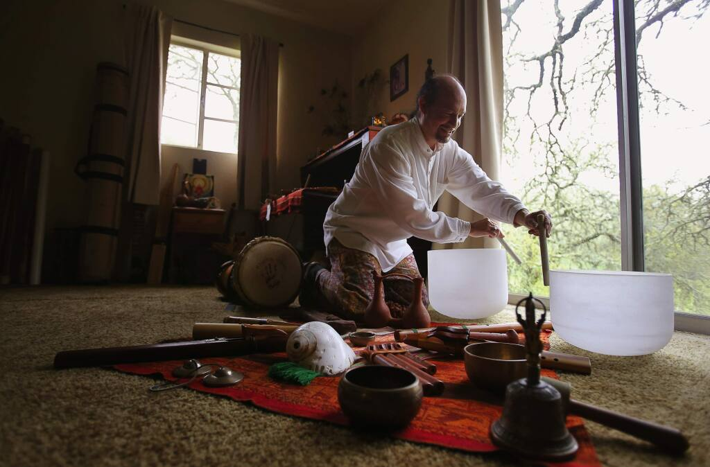 Musician Rene Jenkins demonstrates the use of crystal bowls to create therapeutic sounds at his home in Sonoma, on Thursday, March 10, 2016. (Christopher Chung/ The Press Democrat)