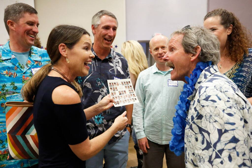 Jim Boyce, right, shows his surprise as his former student Catherine Green gives him a copy of her class picture of the 1983-1984 fifth grade class at St. John Catholic School. Boyce's copy of the photo was destroyed in the Tubbs fire. (Alvin Jornada / The Press Democrat)