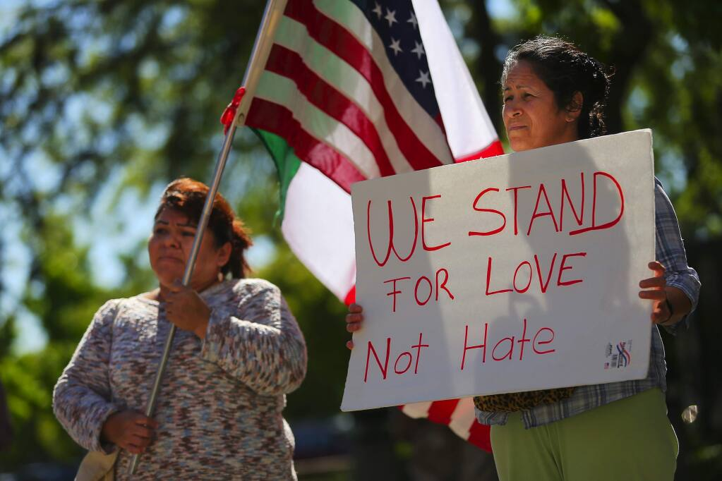 Ana Salgado, left, and Patricia, who declined to provide her last name, participate in an immigration demonstration at the Sonoma County Main Adult Detention Facility, to protest the Sonoma County Sheriff's Office sharing of information of undocumented inmates with the U.S. Immigration and Customs Enforcement, in Santa Rosa on Monday, May 1, 2017. (Christopher Chung/ The Press Democrat)