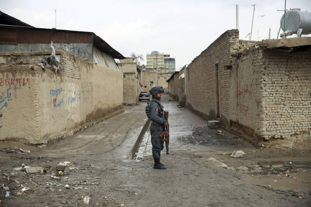 An Afghan security guard stands at the site of an attack in Kabul, Afghanistan, Wednesday, March 25, 2020. Gunmen stormed a religious gathering of Afghanistan's minority Sikhs in their place of worship in the heart of the Afghan capital's old city on Wednesday, a minority Sikh parliamentarian said. (AP Photo/Rahmat Gul)