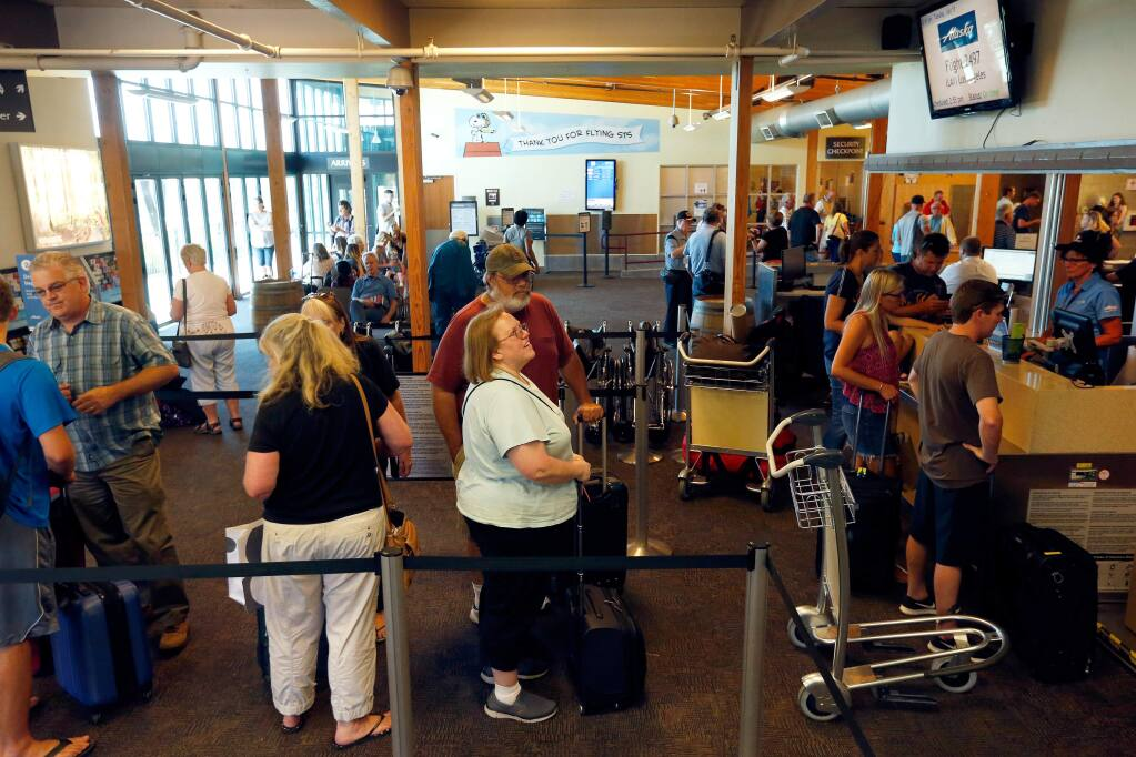 Alaska Airlines passengers check-in for their flights inside the main terminal at Charles M. Schulz-Sonoma County Airport in Santa Rosa, California, on Tuesday, July 11, 2017. (ALVIN JORNADA/ PD)
