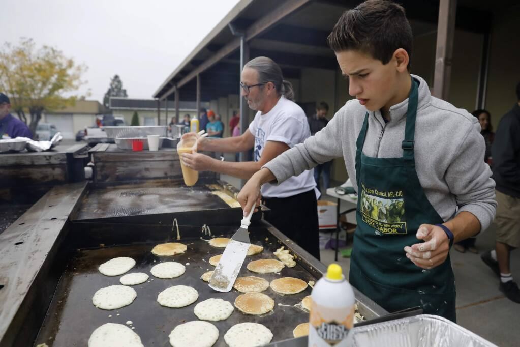 Eighth grader Jackson Boaz, right, and letter carrier Clay Cook cook pancakes and eggs for the buffet line during the North Bay Labor Council's annual Labor Day Pancake Breakfast at the Carpenters' Labor Center on Monday, September 3, 2018 in Santa Rosa, California . (BETH SCHLANKER/The Press Democrat)