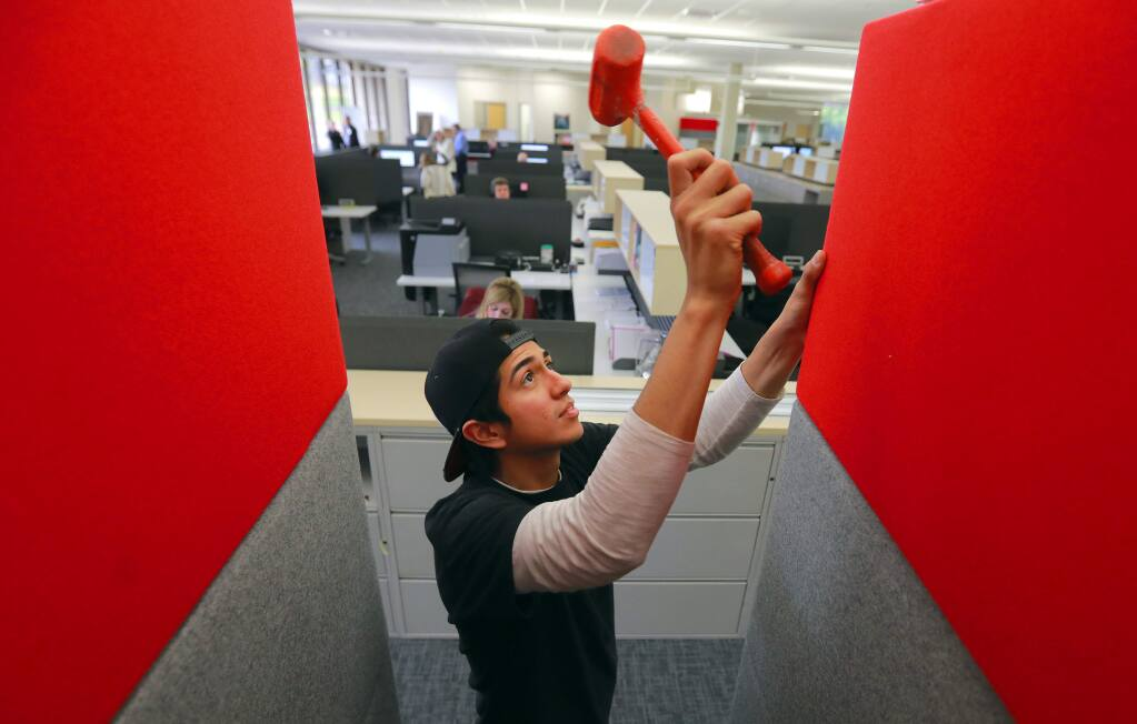 Anthony Ruiz adds panels to small glass cubicles in the renovated main building at Keysight Technologies in Santa Rosa. The measurement equipment company hauled off over 1 million pounds of debris after the October wildfires. (photo by John Burgess/The Press Democrat)
